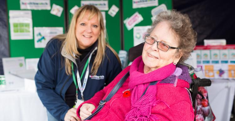 Elderly woman in a wheelchair smiling at the camera at an outdoor event in front of a Healthwatch stand