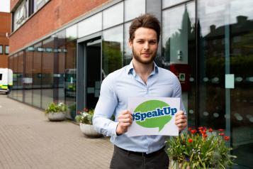 Man holding #Speak Up sign