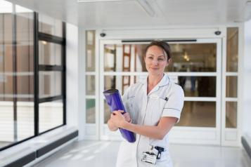 Nurse with a clipboard standing in a hospital corridor