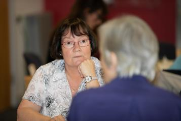 Woman sitting across a table from someone as though in a meeting or at an event