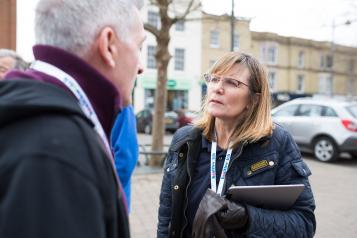 Woman with a Healthwatch lanyard and clipboard speaking to a member of the public outside
