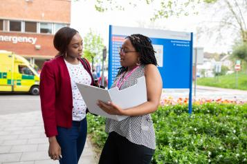 Two women outside a hospital - one has a healthwatch lanyard and is holding a clipboard speaking to the other woman as though asking questions