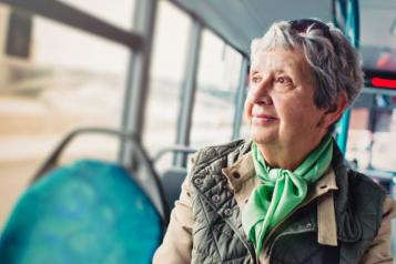 Picture of older woman sitting on a bus looking out the window