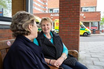 Two older women sitting on a bench talking outside A&E