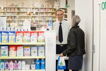 Young woman collecting medication from pharmacist