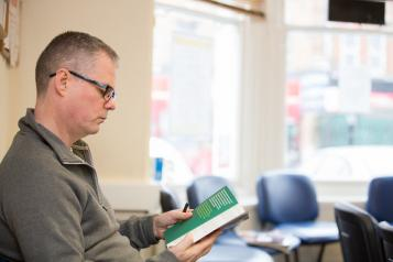 Man sitting on his own in a GP surgery