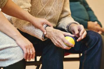 A row of people sitting down with an elderly person holding a ball and someone, possibly a carer, holding their arm
