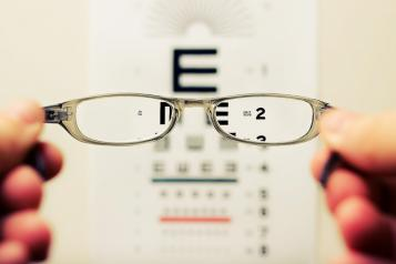 Glasses being held up infront of an eye test