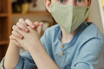 Young boy wearing mask covering lower part of his face