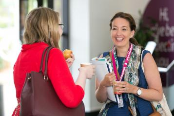 Healthwatch staff members at a conference wearing branded lanyards