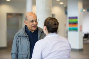 Man speaking to someone working in a health centre