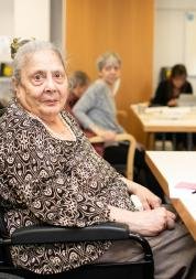 Elderly woman at an engagement event in a wheelchair looking directly at the camera